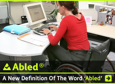 Abled - A New Definition of The Word 'Abled' shows the text against a photo that looks into an office from the rear left quarter behind a woman with reddish brown hair wearing a red long-sleeved blouse and charcoal grey pants working at a computer on a modern white oval desk. The desk is also covered in personal photos and office paraphernalia and the woman is sitting in a modern wheelchair with a black seat, and burnt orange and silver colored wheels.