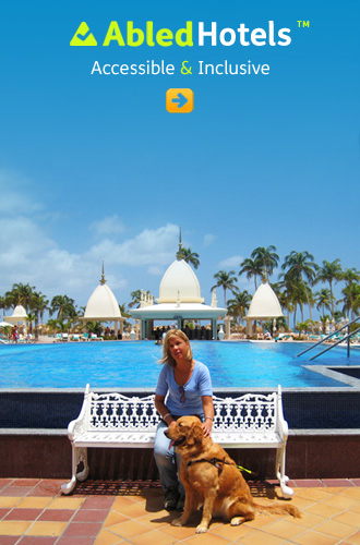 AbledHotels link button shows Laura Meddens sitting on a bench with her guide dog Wagner in front of the swimming pool at the Ruiz hotel and resort in Aruba with white moorish-roofed refreshment bars in the background on a beautiful sunny day