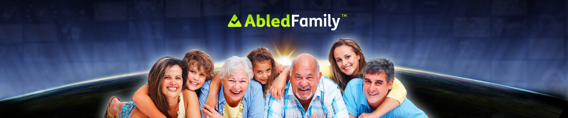 AbledFamily banner shows family members lying on their bellies in the studio facing the camera propped up on their elbows against a backdrop of a a sunrise seen over the curve of the earth and the AbledFamily logo above it.