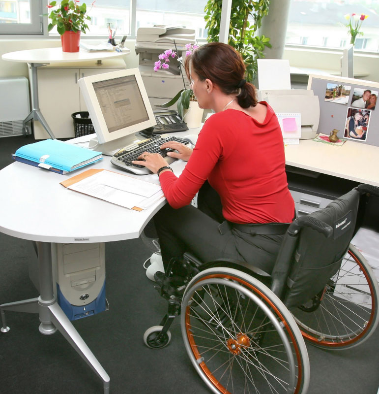 Abled-Definition photo looks into an office from the rear left quarter behind a woman with reddish brown hair wearing a red long-sleeved blouse and charcoal grey pants working at a computer on a modern white oval desk. The desk is also covered in personal photos and office paraphernalia and the woman is sitting in a modern wheelchair with a black seat, and burnt orange and silver colored wheels.