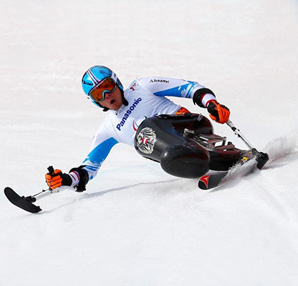 AbledSports photo from Sochi Paralympics shows Roman Rabl of Austria competing in Women's Downhill – Sitting. She is leaning to her right side in her white with blue trim uniform as she extends her right arm and ski pole that has a small ski blade at the bottom and tilts her sitting ski with her left pole.