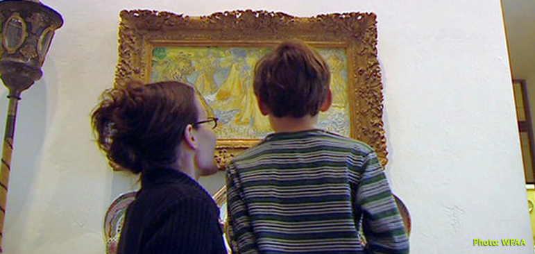Photo shows Ben Pierce and his mother Heidi from behind as Ben sees Vincent van Gogh;s painting of haystacks at the Dallas Museum of Art.