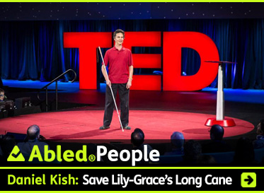 AbledPeople link box shows Daniel Kish standing on a round red-carpeted stage at the 2015 TED Conference in Vancouver. He has dark hair and is wearing a red polo shirt with black trousers and is holding a long white navigation cane. Behind him is a large 3D logo spelling out TED in backlit capital letters. The audience surrounds the stage. The headline reads: Daniel Kish: Save Lily-Grace's Long Cane. Click the box to go to the story.