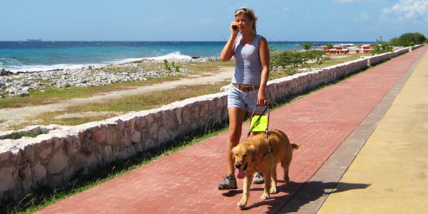 Laura Meddens is shown walking along the oceanfront in Curaçao with her guide dog Wagner while speaking on her mobile phone.