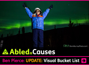 AbledCauses link box shows a photo by RonnMurrayPhoto.com in which 9 year-old Ben Pierce stands with his arms outstretched in a 'victory salute' as the Northern Lights cast a green hue in the sky in the background. Ben is wearing a blue parka with and orange stripe and ivory hood. He wears tinted glasses and is smiling at the camera. The headline reads: AbledCauses: Ben Pierce: UPDATE: Visual Bucket List. Click here to go to the story.