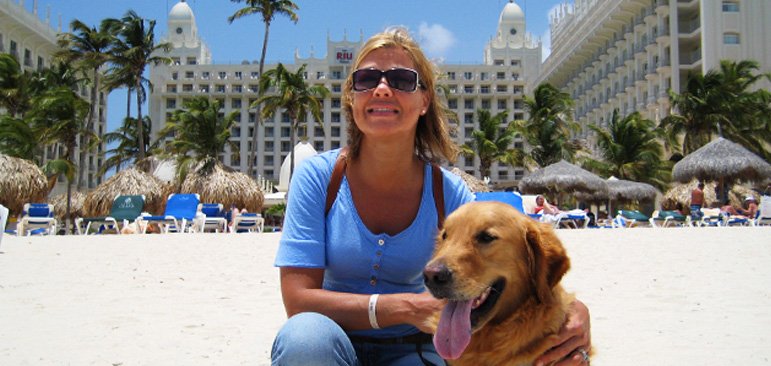 Photo shows Laura Meddens kneeling beside her Seeing EYe Guide dog Wagner, who is a golden retriver on the beach in front of the Riu Palace resort in Aruba. Laura has blond hair and is wearing a baby blue short sleeved t-shirt with silver buttons and blue jeans and a pair of sport sunglasses with black frame with white trim.