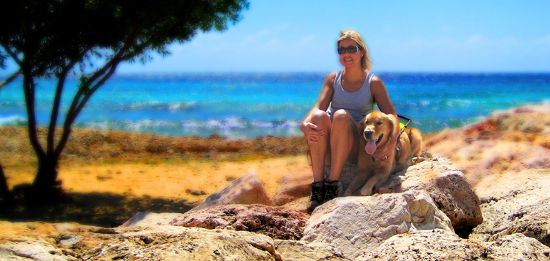 Laura and Wagner are seen sitting on some large coral boulders next to a Divi Divi tree with the turquoise blue Caribbean Sea behind them