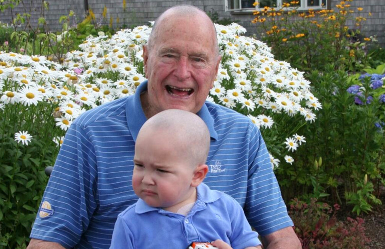 Former President George H. W. Bish poses with two year old Patrick, the son of one of his secret service agents. The boy is battling leukemia and the former president shaved his head in solidarity with the other agents of his security detail to show support for Patrick and his family.