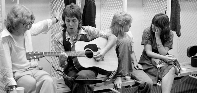 A photo shows Linda Ronstadt sitting on a bench in a changing room chatting with Linda McCartney while Paul McCartney plays a guitar riff for Peter Asher, Ronstadt's producer and former member of the 60's singing duo Peter and Gordon during the 1976 Wings Over America Tour.