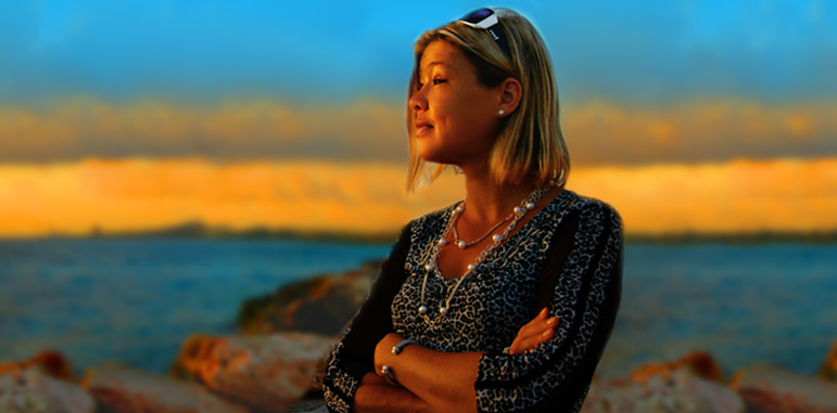 Photo by Jolanta Pawlak shows Abled Co-Founder Laura Meddens looking out at the seaside at sunset in Curaçao. Laura has dark-blonde shoulder length hair with her white and black sports sunglasses perched on top of her head. She is wearing a black and white leopard print blouse with black and leopard-print piping on the sleeves along with a pearl neckalce and pearl earrings. The sunset warms her tanned face with a slightly orange glow while the out-of-focus background shows a line of orange-tinged clouds on the horizon in between the deep turquoise sky and ocean.