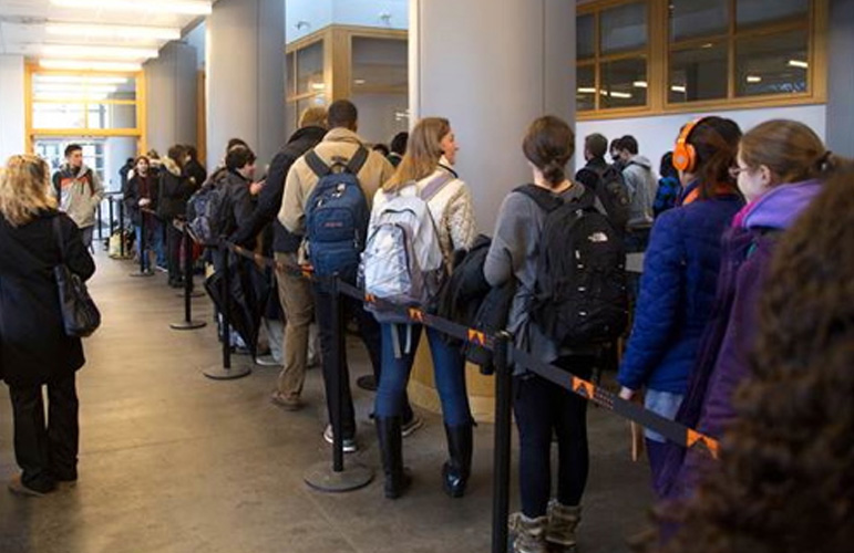Photo provided by Princeton University shows students lined-up in a large hallway with round pillars and between roped-off rows to get the Bexsero vaccination against meningitis B.