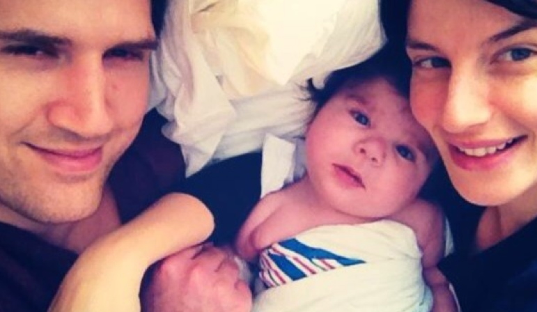 AbledIssues-a family photo shows  Charlie Higgs and Autumn Chenkus lying on a pillow flanking their infant son Maverick.