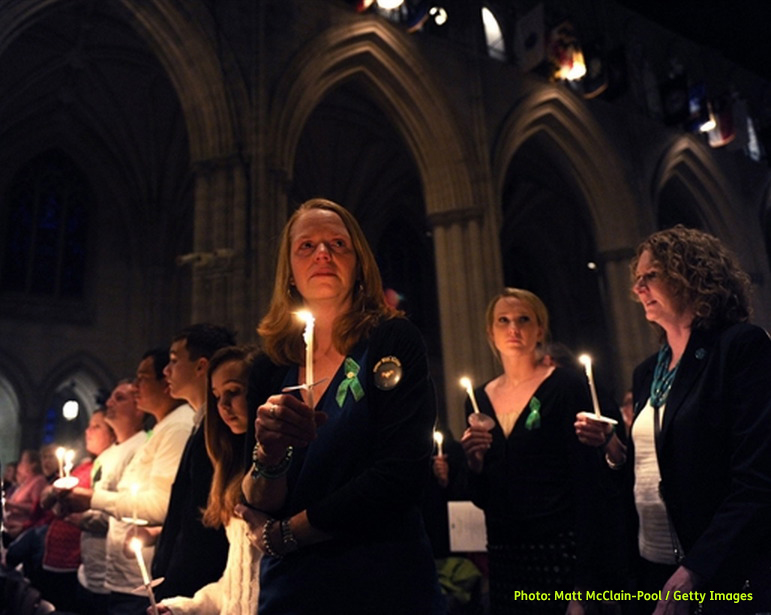 Photo shows Miranda Pacchiana, center, of Newtown, Conn., holding a candle at the end of a National Vigil for Victims of Gun Violence in subdued lighting at Washington National Cathedral on December 12, 2013 in Washington, DC just prior to the next day first anniversary marking the Sandy Hook Elementary School mass shooting.