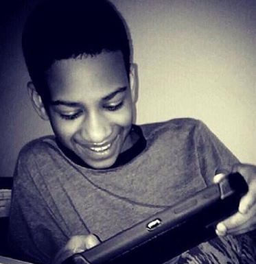 AbledALERT back and white photo of Avonte Oquendo smiling and looking down at a tablet computer he is holding.