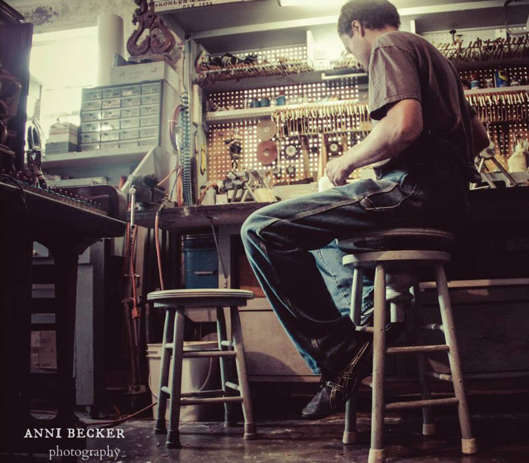 AbledCauses photo by Anni Becker shows John Furniss sitting on a wooden stool in the piano restoration shop with a rack of tools above the workbench to his right with an old upright piano about two feet in front of him. John has brown hair and is wearing bluejeans and a brown t-shirt.