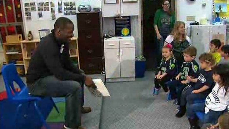 A screenshot from an NBC News feature on Derrick Coleman shows the Seattle Seahawks fullback visiting 'Listen and Talk' a program for kids with hearing loss. Many of the children are wearing Seattle Seahawks jerseys.