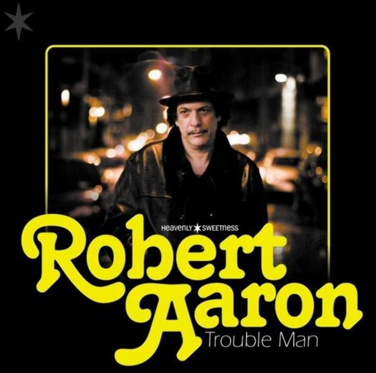 AbledCoping photo shows an album cover of Robert Aaron titled Trouble Man - which shows Aaron wearing a fedora hat and a leather jacket in the middle of a street at night. He has dark brown hear and a mustache. His real name is Robert Vineberg and he has been arrested after being found in his apartment with a stash of heroin bags suspect in the death of Philip Seymour Hoffman.
