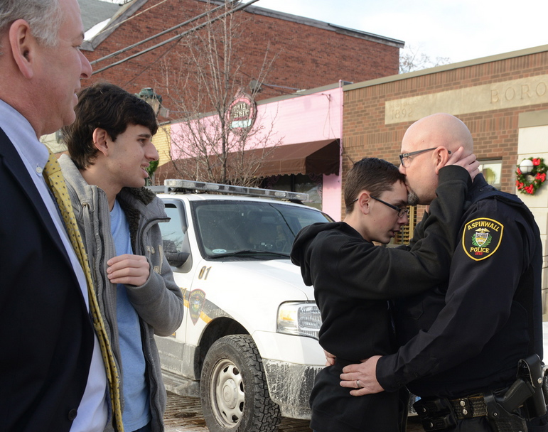 AbledResponders photo taken by Bill Wade of post-gazette.com shows Aspinwall police Officer Scott Bailey saying goodbye to his son Trevor, 15, by embracing him and kissing his forehead as Tom Swan, Allegheny County deputy district attorney, with his son Kevin, left, watch after a group photo was taken outside the Aspinwall Police Department. Both teens are autistic, as is Officer Bailey's other son, Trent. The two families are part of a training video for police.