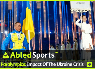 AbledSports Post Banner shows a photo of Biathlete Mikhaylo Tkachenko, the flag bearer for the Ukrainian Paralympic team wearing their blue uniform with a yellow torso, and with the blue and yellow flag of Ukraine mounted on his wheelchair as he enters the Olympic stadium in Sochi to thunderous applause during the opening ceremonies of the 2014 Sochi Winter Paralympic Games. The headline reads:AbledSports: Paralympics: Impact of the Ukraine Crisis. Click here to go to the post.