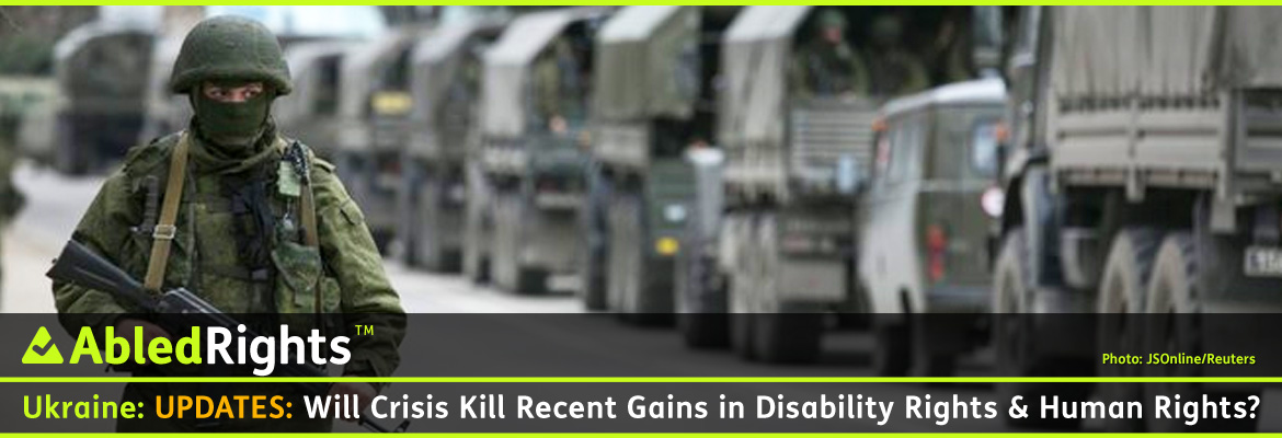 AbledRights Post Banner shows a photo of an armed serviceman in-focus in the foreground standing on a sidewalk as a convoy of Russian army vehicles is out-of focus as it drives past him outside a Ukrainian border guard post in the Crimean town of Balaclava.