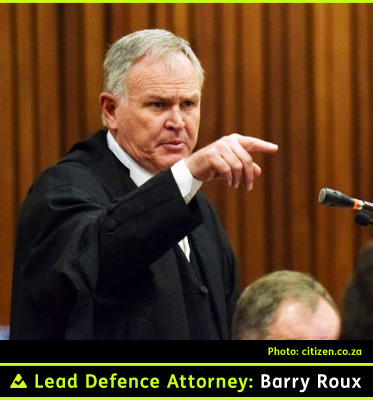 AbledNews Photo of Lead Defence Attorney Barry Roux who is also wearing black legal robes and gesturing with his right arm and index finger at the courtroom podium in Pretoria's High Court. He has salt and pepper hair with a high receding hairline.