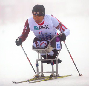 AbledSports photo from the Sochi Paralympics shows Kozo Kubo of Japan strapped in as he kneels in his double ski housing as he competes in the Men's Biathlon 12.5 kilometre - Sitting.