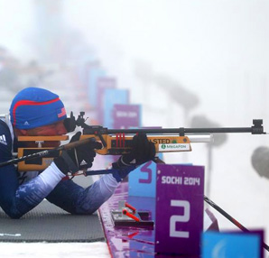 AbledSports photo from Sochi Olympics Biathlon shows Sean Halsted of the USA aiming a rifle as he competes in the Men's Biathlon 12.5km - Sitting.