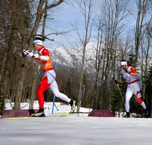 AbledSports photo from the Sochi Paralympics shows Brian McKeever of Canada being led by his guide Erik Carleton as he competes in the men's 20km visually impaired cross-country skiing. They are dressed in the red and white uniforms of the Canadian team and are moving from the right to left in the photo with trees and snow-capped mountains in the background on a sunny day.