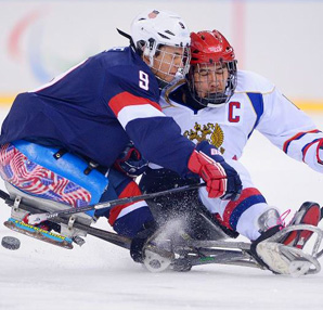 AbledSports photo from Sochi shows Andy Yohe of the United States and Dmitrii Lisov of Russia as they battle for the puck during the Ice Sledge Hockey Preliminary Round Group B match.