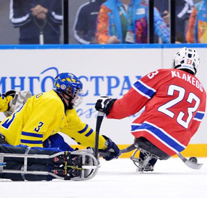 AbledSports photo from Sochi shows Jan Roger Klakegg of Norway missing a chance at goal during the Ice Sledge Hockey Preliminary Round Group A match between Norway and Sweden.
