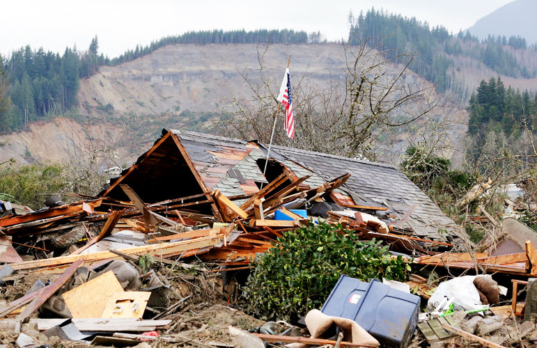Photo shows the collapsed rooftop of Mac McPherson's house with an American Flag on a pole rising out of a hole in the rooftop. The so-called headscarp or cliff left behind by the mudslide is visible in the background. Pool photo by Ellaine Thompson of the Associated Press.