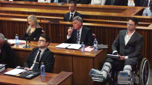 AbledNews photo of Oscar Pistorius listening to the verdict being read in court. His brother Carl sits in a row in front of him in a wheelchair after being badly injured in a high speed car crash.