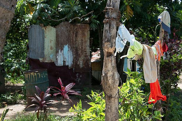Photo from the Pan American Health Organization series by Luz Sosa shows laundry hanging in a yard in the Dominican Republic with a barrel nearby used to catch rainwater for washing. However these rain barrels become breeding grounds for infectious mosquitoes that can carry Dengue Fever as well as Chikungunya.