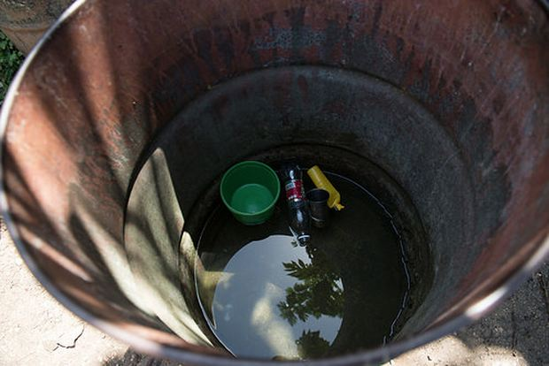 Photo by Luz Sosa shows a closeup of the standing water inside a rain barrel used to collect water for washing clothing in the Dominican Republic.