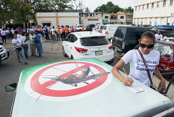 Photo by Luz Sosa shows a young woman filling out a form on the roof of the pickup truck pictured in the previous photo as part of a 'National Day Against Chikungunya' in the Dominican Republic. More people are seen in the background at the event.