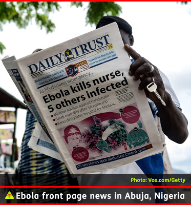 AbledALERT photo shows a man standing and reading a newspaper in Abuja, Nigeria where headlines about Ebola cover the front page of the Daily Trust newspaper.
