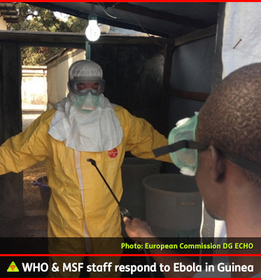 AbledALERT photo shows a Doctor from Doctors without Borders in a yellow protective suit and white protective headgear getting sprayed with disinfectant by a local health worker who is wearing protective goggles in Guinea.