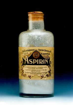 Photo shows a vintage bottle of Bayer Aspirin from 1889. It contains a bit of white powder and has a beige label around the outside middle of the bottle with artwork of the era.