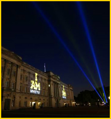 AbledWarriors - Invictus Games- A photo taken at night shows the words I AM INVICTUS being projected on the front facade of Buckingham Palace in two places while two blue strobes from a laser are seeing in the sky nearby.