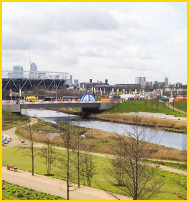 AbledWarriors Invictus Games shows Queen Elizabeth Olympic Park with London office towers off in the distance behind the Olympic stadium and walking trails among the grass and trees.