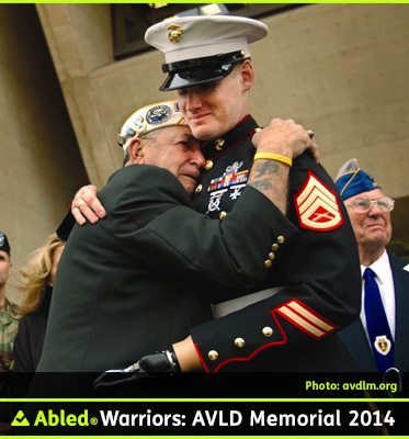 AbledWarriors F A Q photo for The Experience shows an elderly veteran crying on the shoulder of a younger U.S. Marine veteran who is in full dress uniform and uses a prosthetic hook in place of his left hand.
