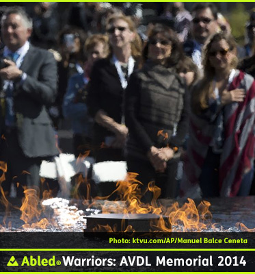AbledWarriors-Photo-Invites guests and veterans are seen behind a flame from a pool as they listen to President Barack Obama speak at the American Veterans Disabled for Life Memorial dedication ceremony in Washington, Sunday, Oct. 5, 2014.