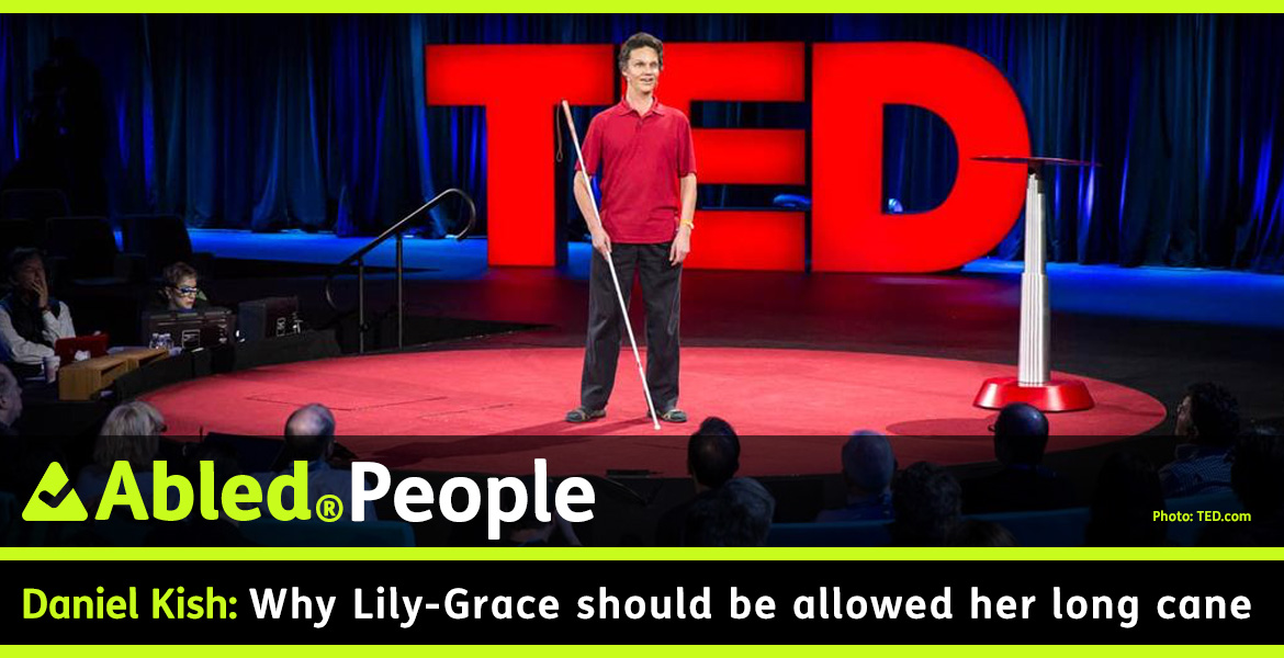 AbledPeople Post-banner shows Daniel Kish standing on a round red-carpeted stage at the 2015 TED Conference in Vancouver. He has dark hair and is wearing a red polo shirt with black trousers and is holding a long white navigation cane. Behind him is a large 3D logo spelling out TED in backlit capital letters. The audience surrounds the stage. The headline reads: Daniel Kish: Why Lily-Grace should be allowed her long cane.