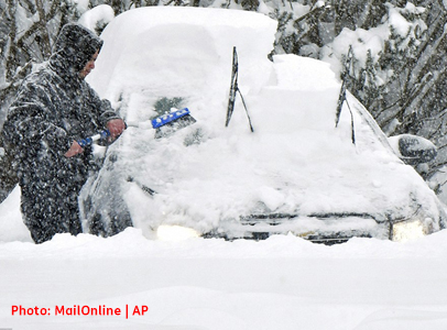 Photo shows man trying to clear heavy snow from buried vehicle.