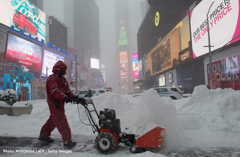 Photo of a man using a snowblower in Times Square in New York City.