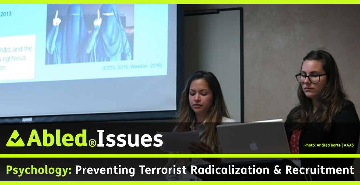 AbledIssues: Psychology: Preventing Terrorist Radicalization & Recruitment. Image: Photo shows two female forensic psychologists making a presentation on the subject. A photo of two women wearing burqas is project on the screen behind them.