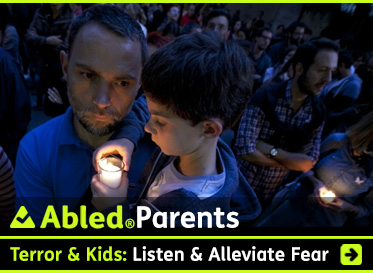 AbledParents link box shows a photo of a father holding his son close among other people at a candlelight vigil in Mexico City for the victims of the Paris terror attack. The boy is holding and looking at a candle burning in a glass jar. Click on the banner to go to the story.