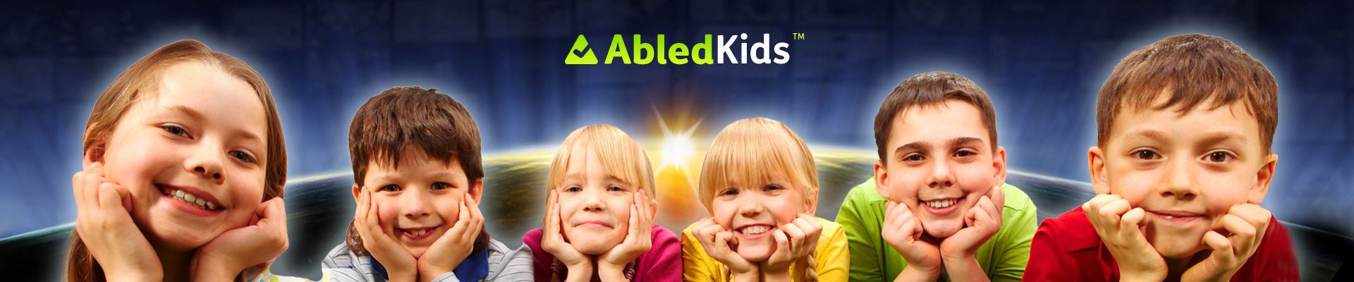 AbledKids Banner shows 6 children facing the camera lying on their bellies with their faces resting on their upturned hands