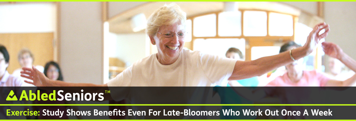 AbledSeniors Post Banner shows an older woman with white hair with glasses wearing a white t-shirt smiling as she stretches her arms out to her side as part of an exercise class while you see her classmates in the background with bright light from outside streaming in behind them through arched pane windows above the door to the gym.