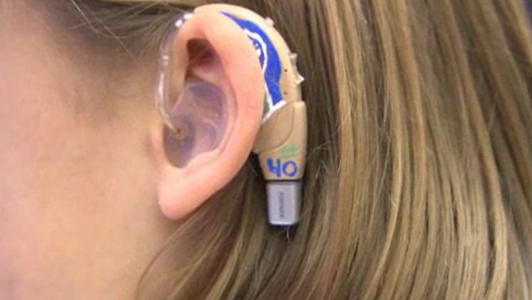 AbledPeople photo shows a close up of a hearing aid on the ear of of a young girl at the Listen and Talk non-profit in Seattle. The hearing aid has e decal of the Seattle Seahawks logo with the number 40 painted on it in honor of Seahawks fullback Derrick Coleman.
